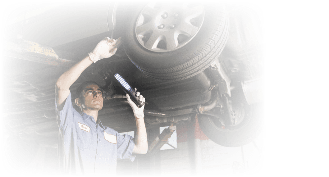 Mechanic inspecting the underside of a vehicle