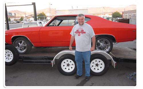Mechanic Mike Palmer standing with a muscle car taken care of at Mike Palmer Automotive